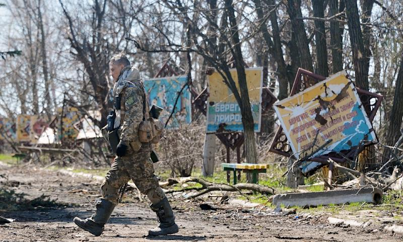 A Ukrainian serviceman walks along a path with marks from shelling in Shirokine village on April 15, 2015, on the outskirts of the strategic port city of Mariupol