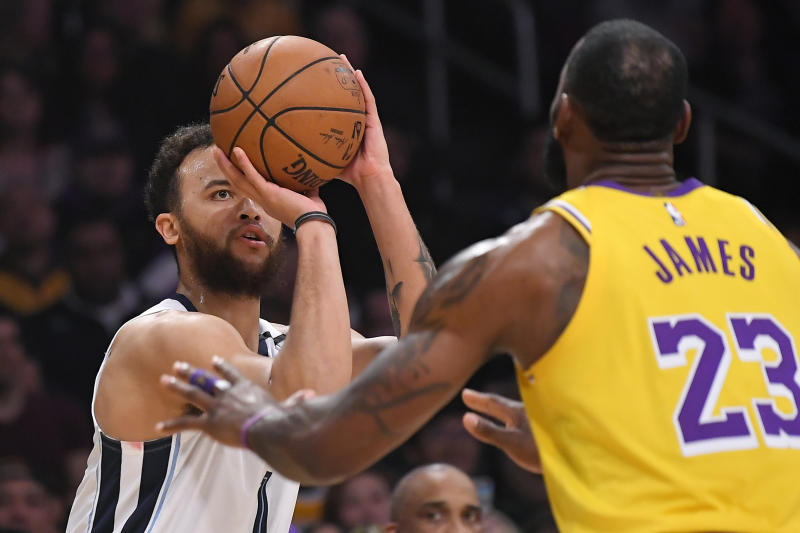 Memphis Grizzlies forward Kyle Anderson, left, shoots as Los Angeles Lakers forward LeBron James defends during the first half of an NBA basketball game Friday, Feb. 21, 2020, in Los Angeles. (AP Photo/Mark J. Terrill)