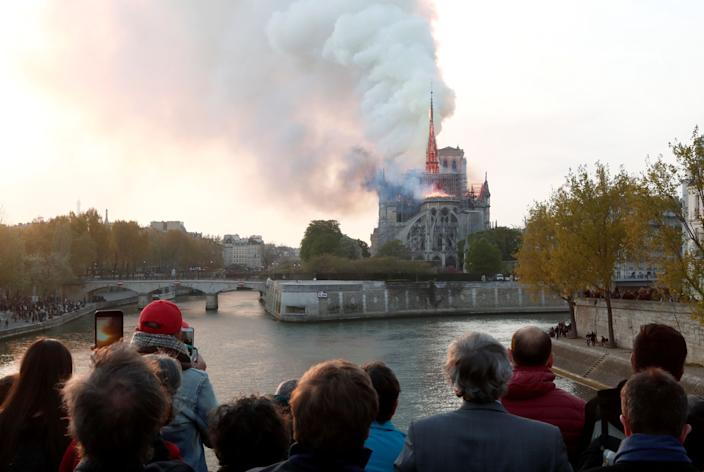 People watch from a bridge as smoke billows from Notre Dame Cathedral during a fire in Paris, France April 15, 2019. (Photo: Benoit Tessier/Reuters)