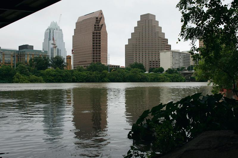 """A part of the city skyline is reflected in Town Lake Thursday, July 26, 2007, in Austin, Texas. The city council is to rename it """"Lady Bird Lake,"""" in honor of Lady Bird Johnson who died on July 11, 2007. The former first lady was an early supporter of environmental issues and known for her efforts toward beautification of the nation's countryside. The lake is filled with impounded waters of the Colorado River. (AP Photo/Harry Cabluck)"""
