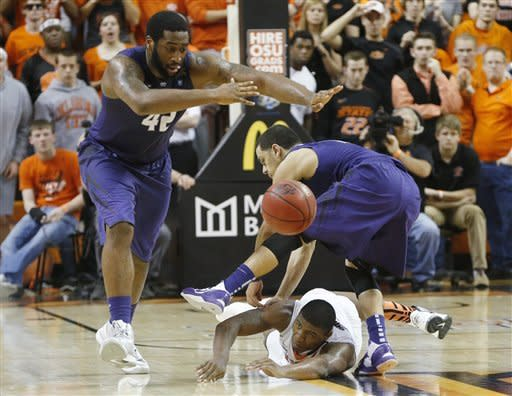 Kansas State forward Thomas Gipson (42), guard Angel Rodriguez (13) and Oklahoma State guard Marcus Smart (33) watch a loose ball in the second half of an NCAA college basketball game in Stillwater, Okla., Saturday, March 9, 2013. Oklahoma State won 76-70. (AP Photo/Sue Ogrocki)