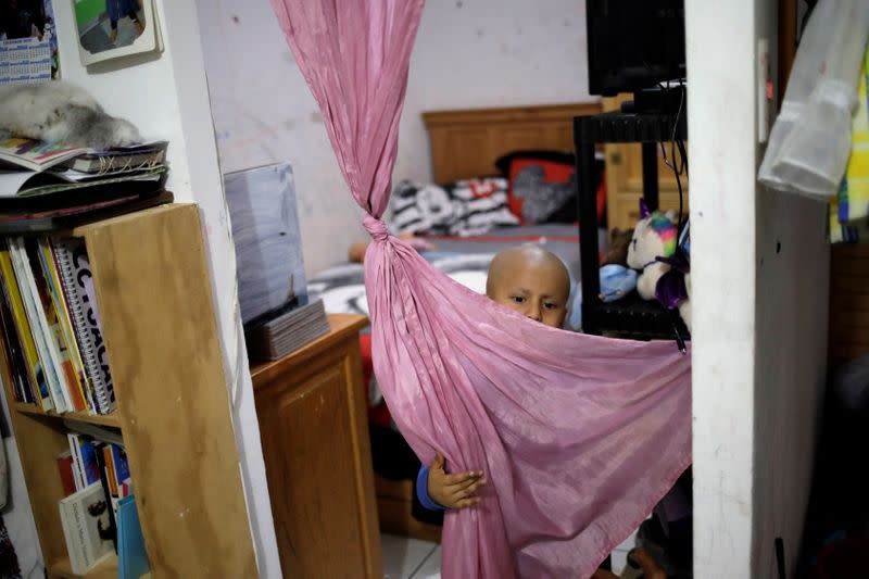 Hermes Soto plays with a curtain at his house in Mexico City