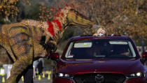 Samantha Bailey is watched by a moving raptor worn by Jose Correa at the Jurassic Quest Drive-Thru Experience on Friday, Jan. 15, 2021, at the Rose Bowl in Pasadena, Calif. The touring exhibit features over 70 moving and life-like dinosaurs, and runs through January 31. (AP Photo/Chris Pizzello)