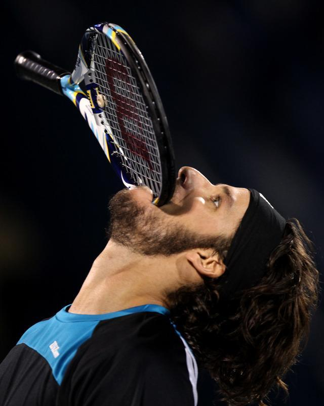 Feliciano Lopez of Spain bites his racket after losing to Swiss champion Roger Federer during their ATP Dubai Open tennis match in the Gulf emirate on February 29, 2012. Federer won the match 7-5, 6,3. TOPSHOTS/(Photo by Marwan Naamani/AFP/Getty Images)