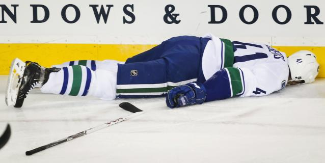 Vancouver Canucks' Andrew Alberts lies motionless on the ice after being hit by Calgary Flames' Brian McGrattan during the first period of an NHL hockey game in Calgary, Alberta, Sunday, Dec. 29, 2013. (AP Photo/The Canadian Press, Jeff McIntosh)