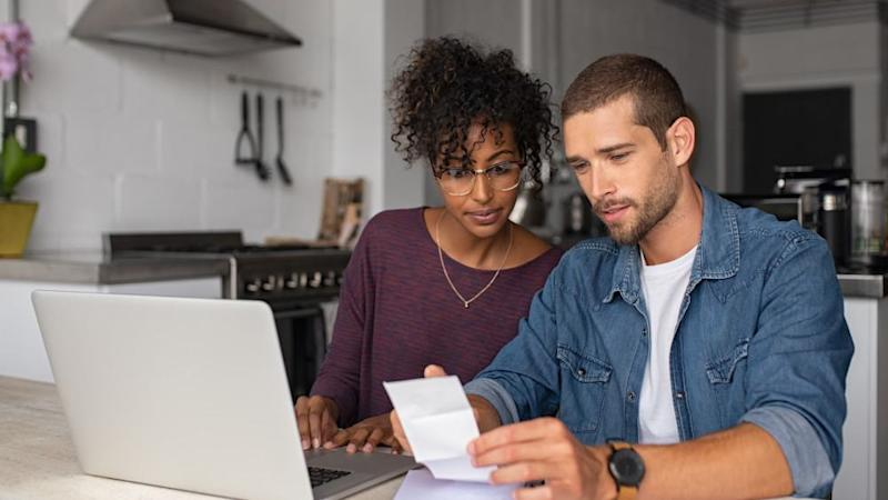 Young casual man and girl using laptop while looking at invoice and plan the budget to save.