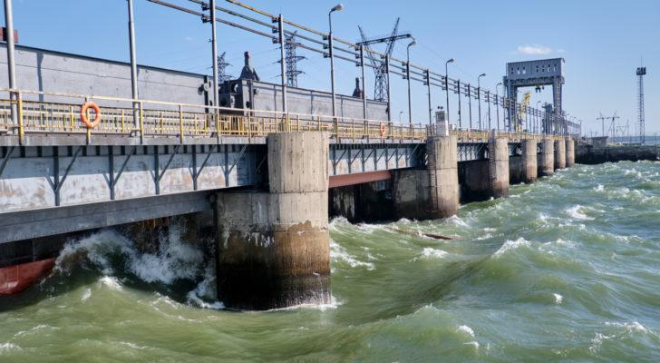 A hydroelectric power plant operates in a river with large waves crashing against the side.