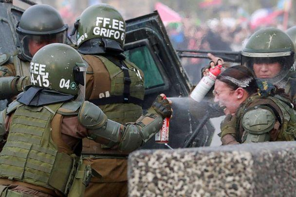 PHOTO: A riot police officer that was on fire is assisted by colleagues during a protest against Chile's government in Santiago, Chile, Nov. 4, 2019. (Henry Romero/Reuters)