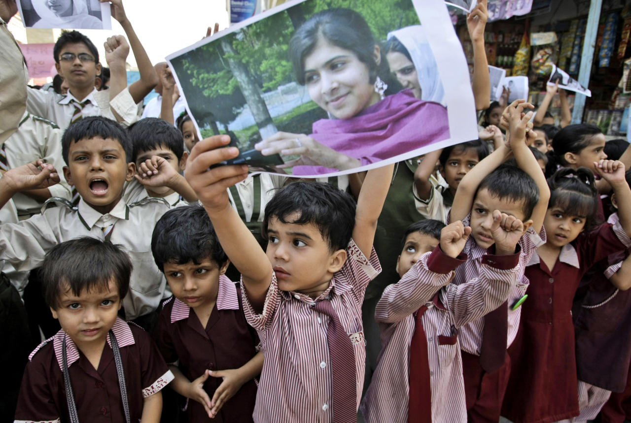 A Pakistani boy holds up a picture of 14-year-old schoolgirl Malala Yousufzai, who was shot last Tuesday by the Taliban for speaking out in support of education for women, while he and other schoolchildren attend a protest condemning the attack, in Karachi, Pakistan, Saturday, Oct. 13, 2012. (AP Photo/Fareed Khan)