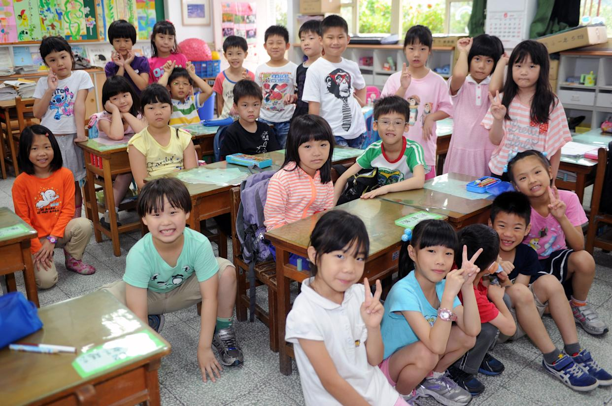 Elementary school student Ryan Kao (bottom left), 7, poses for a photo with his classmates at school in Taipei on June 5, 2013.