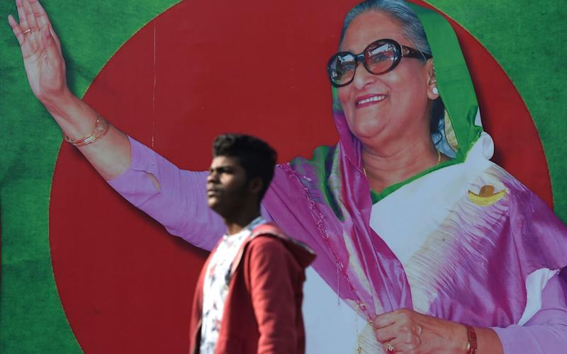 A Bangladeshi man walks past a photo of Prime Minister Sheikh Hasina, in Dhaka on December 29, 2018 - AFP