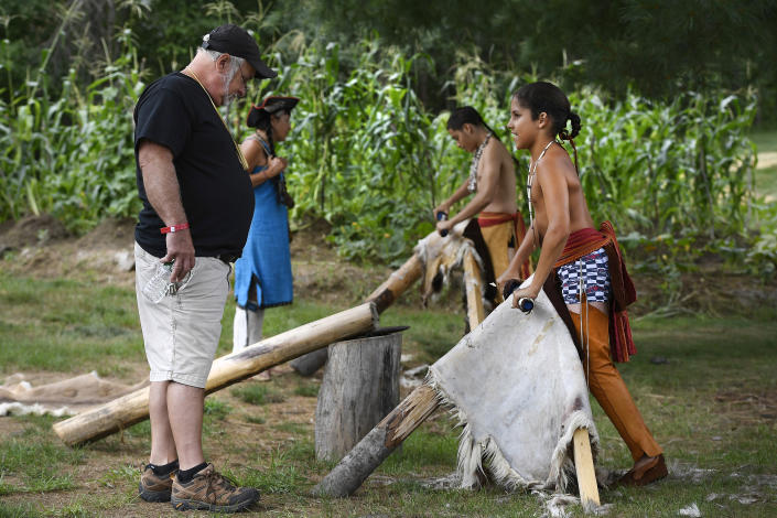 William Small Ear Coyote of Grafton, Mass., and a member of the Nipmuc Nation, right, talks with Joseph Soares of Acadia, R.I., left, as he demonstrates flashing of an animal skin at Eastern Woodland Village during Schemitzun on Mashantucket Pequot Reservation, in Mashantucket, Conn., Saturday, Aug. 28, 2021. Connecticut and a handful of other states have recently decided to mandate students be taught about Native American culture and history. (AP Photo/Jessica Hill)
