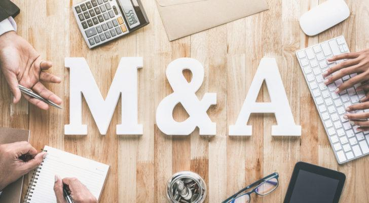 """The letters """"M&A"""" on top of a wooden table surrounded by hands, a keyboard, notepad and calculator."""