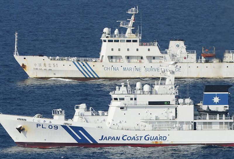 FILE - In this Oct. 25, 2012 file photo, ships of China Marine Surveillance and Japan Coast Guard steam side by side near disputed islands, called Senkaku in Japan and Diaoyu in China, in the East China Sea. Chinese patrol boats have harried the Japanese Coast Guard many times a week for more than a month in an unusually relentless response to their latest maritime spat. China says ships from its Marine Surveillance service are merely defending Chinese sovereignty and protesting illegal Japanese control over the uninhabited islands, known as Senkaku in Japan and Diaoyu in China. (AP Photo/Kyodo News, File) JAPAN OUT, MANDATORY CREDIT, NO LICENSING IN CHINA, FRANCE, HONG KONG, JAPAN AND SOUTH KOREA