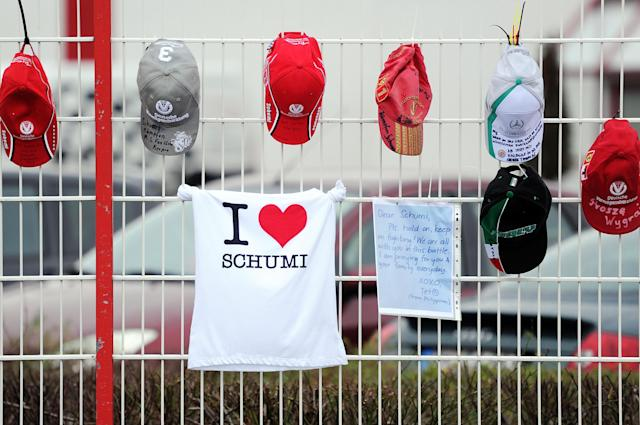 Schumacher fan caps, a fan T-shirt and a letter are attached on the fence at the Michael Schumacher Cart Center in his home town Kerpen, western Germany, Friday, Jan. 3, 2014. The Formula One record world champion is still in a coma after his skiing accident in France. (AP Photo/dpa, Marius Becker)