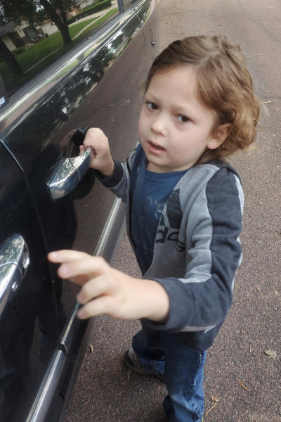 In this Thursday Aug. 22, 2019 photo provided by George Hendrickson, his son, Eliyah, waits to enter his father's truck for the first day of school in Harrisburg, S.D. The 7-year-old has been diagnosed with Dravet syndrome and his father would like to see the state approve medical marijuana to aid in his treatment. Volunteers are gathering signatures to get an initiated measure on the November ballot. (George Hendrickson via AP)