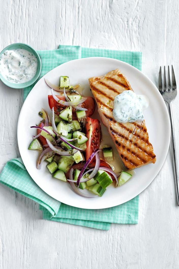 """<p>Grilled salmon pairs perfectly with an herb salad and lemon tzatziki. </p><p><em><a href=""""https://www.womansday.com/food-recipes/food-drinks/recipes/a54835/grilled-salmon-with-greek-salad-recipe/"""" rel=""""nofollow noopener"""" target=""""_blank"""" data-ylk=""""slk:Get the Grilled Salmon with Greek Salad recipe."""" class=""""link rapid-noclick-resp"""">Get the Grilled Salmon with Greek Salad recipe.</a></em></p>"""