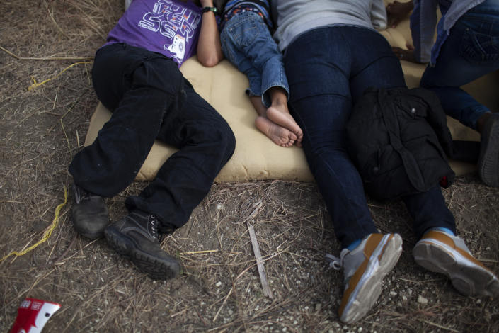 Honduran migrants rest on the side of the road near a police roadblock at a highway in Vado Hondo, Guatemala, Guatemala, Sunday, Jan. 17, 2021. Guatemalan police and soldiers have used tear gas and wielded batons and shields against a group of Honduran migrants that tried to push through their roadblock. (AP Photo/Sandra Sebastian)