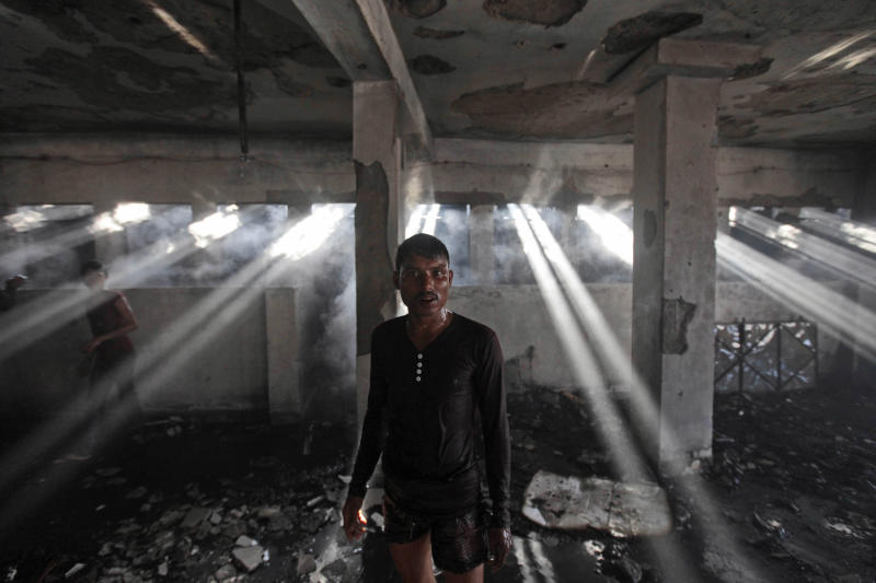 A Bangladeshi worker walks inside a two-storied garment factory that caught fire in Dhaka, Bangladesh, Saturday, Jan.26, 2013. The fire swept killed at least six female workers and injured another five, police and fire officials said. The latest fire occurred more than two months after a deadly fire killed 112 workers in another factory near the capital city, raising questions about the safety measures in Bangladesh garment industry. (AP Photo/A.M. Ahad)