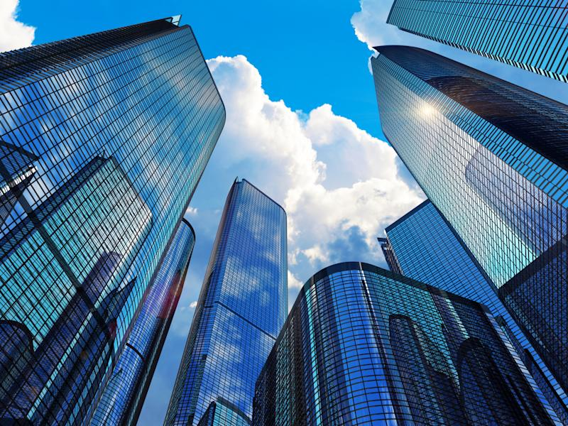 A group of skyscrapers against a sunny sky.