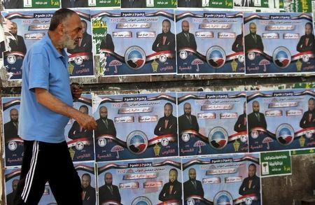 Man walks past election posters for parliamentary candidates of the Nour party Hossam Abdo and Mohammed Osama in the Imbaba district of Giza, Egypt