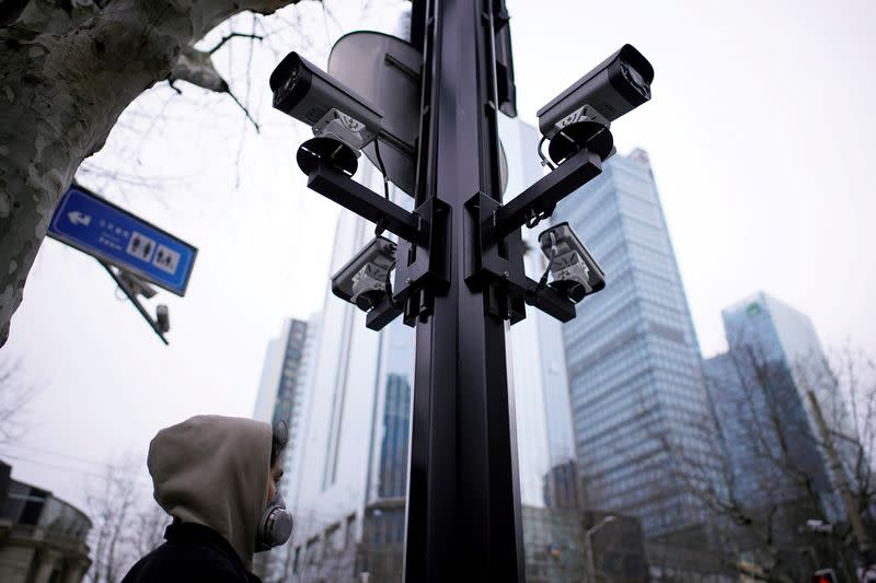 FILE PHOTO: A man wearing a protective face mask walks under surveillance cameras as the country is hit by an outbreak of the novel coronavirus, in Shanghai