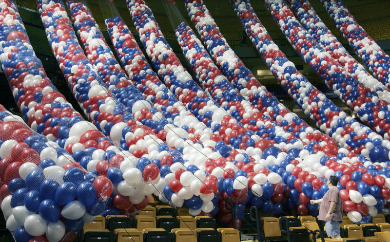 FILE - This July 20, 2004 file photo shows a worker adjusting some of the thousands of balloons, as they prepare to lift the balloons to the ceiling in the Fleet Center, the site for the 2004 Democratic Convention in Boston. With a threat of rain, there will be no downpour of balloons. A Democratic convention official says the finale at the Democratic National Convention will miss the traditional massive balloon drop after President Barack Obama delivers his nomination acceptance speech. (AP Photo/Ron Edmonds, File)