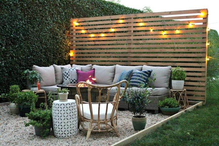 """<p>Create a comfy backyard living space with a plush sofa and pillows, tons of potted plants, and a privacy fence made out of wooden pallets. String lights help change the fence from a boring backdrop to an inspiring installation.</p><p><strong>See more at </strong><strong><a href=""""https://cityfarmhouse.com/2017/08/new-modern-rustic-outdoor-privacy-screen-the-rest-of-my-patio.html"""" rel=""""nofollow noopener"""" target=""""_blank"""" data-ylk=""""slk:City Farmhouse"""" class=""""link rapid-noclick-resp"""">City Farmhouse</a></strong><strong>.</strong></p><p><a class=""""link rapid-noclick-resp"""" href=""""https://go.redirectingat.com?id=74968X1596630&url=https%3A%2F%2Fwww.homedepot.com%2Fs%2Fprivacy%252520fence%252520panels&sref=https%3A%2F%2Fwww.countryliving.com%2Fgardening%2Fnews%2Fg3404%2Fbackyard-string-lights%2F"""" rel=""""nofollow noopener"""" target=""""_blank"""" data-ylk=""""slk:SHOP PRIVACY FENCES"""">SHOP PRIVACY FENCES</a></p>"""