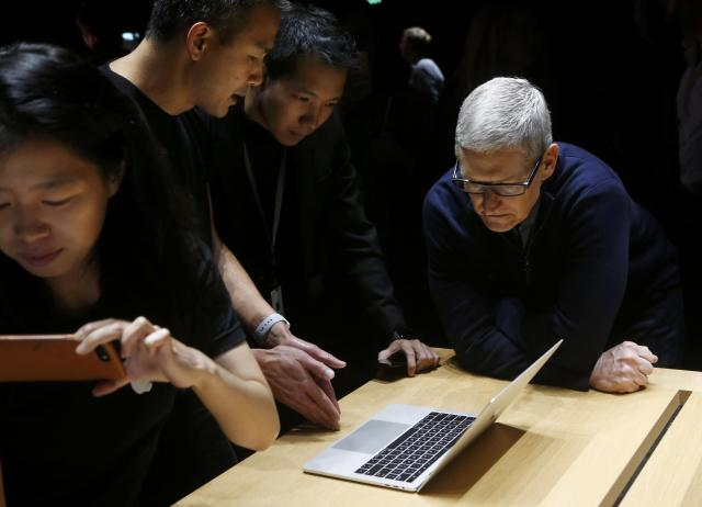 Apple CEO Tim Cook (R) views the MacBook Pro in the demo room after an Apple media event in Cupertino, California, U.S. REUTERS/Beck Diefenbach