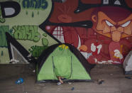 A homeless person's feet hang outside a tent set up under a road bridge, amid the new coronavirus pandemic in Sao Paulo, Brazil, Wednesday, Jan. 27, 2021. (AP Photo/Andre Penner)