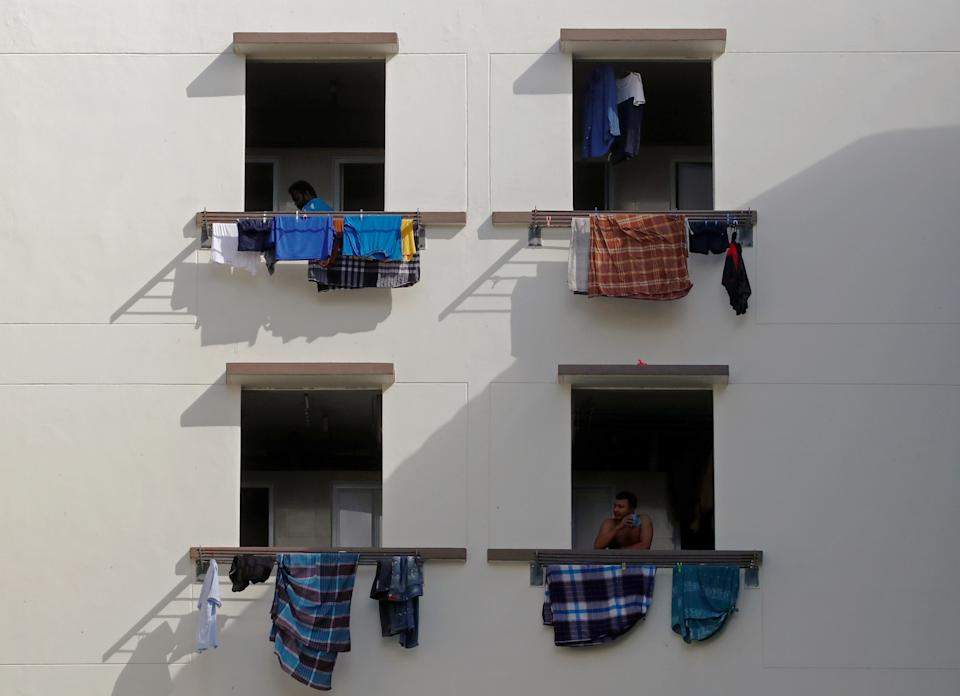 Migrant workers look out of windows in a dormitory, amid the coronavirus disease (COVID-19) outbreak in Singapore May 15, 2020.  REUTERS/Edgar Su