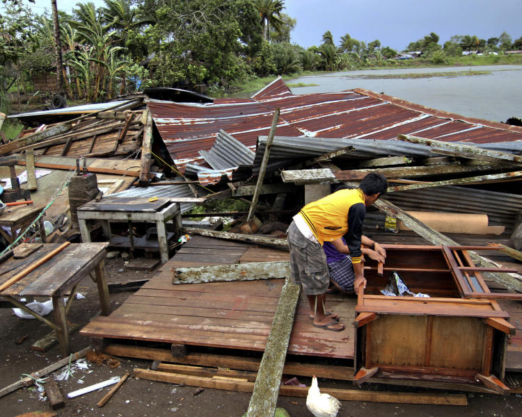 Residents prepare to assess their house which was damaged by Typhoon Bopha in Butuan city in southeastern Philippines Tuesday Dec. 4, 2012. A Philippine governor says at least 33 villagers and soldiers have drowned when torrents of water dumped by the powerful typhoon rushed down a mountain, engulfing the victims and bringing the death toll from the storm to about 40. (AP Photo/Erwin Mascarinas)