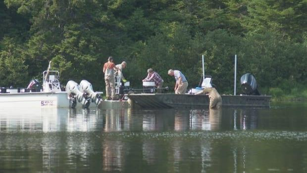 Crews remove barrels of rotenone from boats to be taken away after days of delays caused by Wolastoqey grandmothers and mothers paddling on the lake. (Shane Fowler/CBC - image credit)