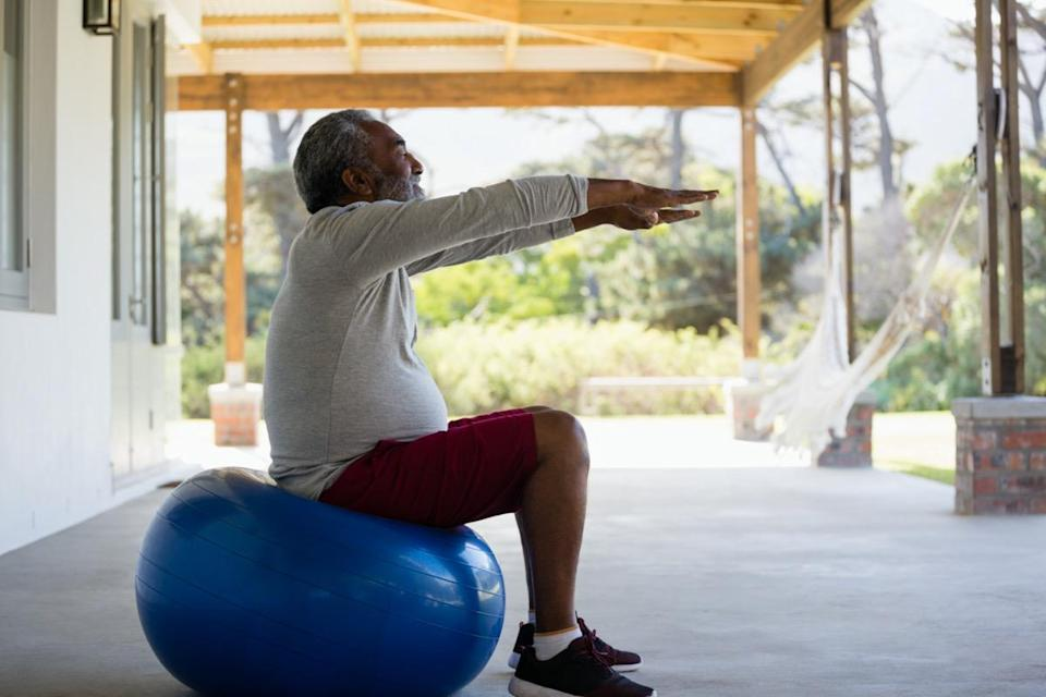 Active senior man exercising on exercise ball in the porch