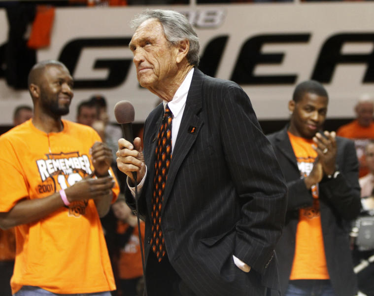 FILE - In this Wednesday, Jan. 26, 2011, file photo, former Oklahoma State coach Eddie Sutton, center, talks to fans during a ceremony honoring the 10th anniversary of the death of 10 members of the Oklahoma State basketball program in a plane crash, at halftime of an NCAA college basketball game between Oklahoma State and Texas in Stillwater, Okla. Sutton, the Hall of Fame basketball coach who led three teams to the Final Four and was the first coach to take four schools to the NCAA Tournament, died Saturday, May 23, 2020. He was 84. (AP Photo/Sue Ogrocki, File)