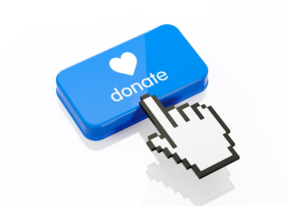 Hand shaped computer cursor is clicking on a blue computer button on white reflective surface. Donate writes on button. Horizontal composition with copy space and clipping path.  Donation and charity concept.