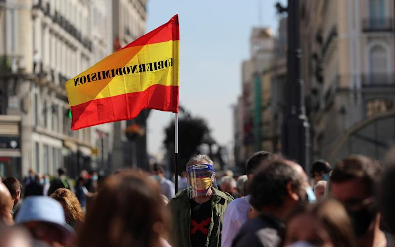 A protester wears a face mask depicting the Spanish national flag during a demonstration against mobility restrictions in 37 areas of Madrid - Rodrigo Jimenez/Shutterstock
