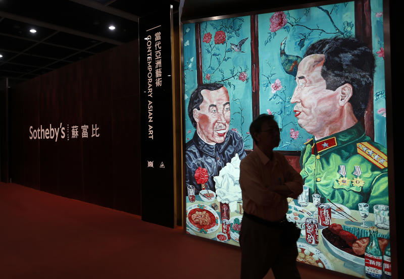 """A man walks past a poster of a painting """"Revolutionary Family Series – Invitation to Dinner"""" by Chinese artist Liu Wei at the Sotheby's autumn auction in Hong Kong Monday, Oct. 8, 2012. The work sold for US$2.24 million set a world auction record for the artist. (AP Photo/Vincent Yu)"""