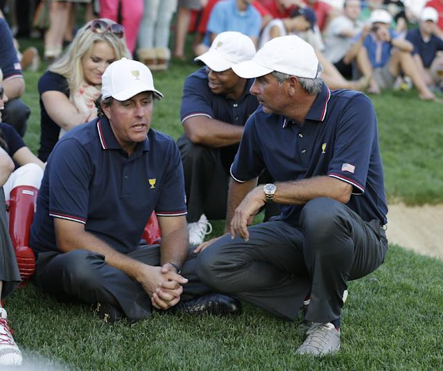 U.S. captain Fred Couples talks player Phil Mickelson during a four-ball match at the Presidents Cup golf tournament at Muirfield Village Golf Club on Thursday, Oct. 3, 2013, in Dublin, Ohio. Mickelson and Keegan Bradley lost their match to International's Louis Oosthuizen and Charl Schwartzel. (AP Photo/Darron Cummings)