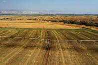 Agricultural fields are seen near the border with Jordan (background). Assessments show Israel does not have enough land to ramp up the necessary solar production to meet its Paris accord commitments, so it will have to buy solar power from Jordan (AFP/MENAHEM KAHANA)