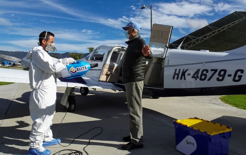 A man using protective gear disinfects a passenger before boarding a plane that collects samples of the corovirus disease (COVID-19) in villages with difficult access, in Bogota