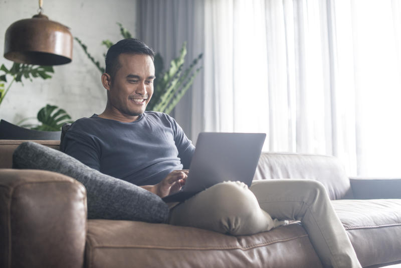 Smiling man sitting on couch, typing on laptop.