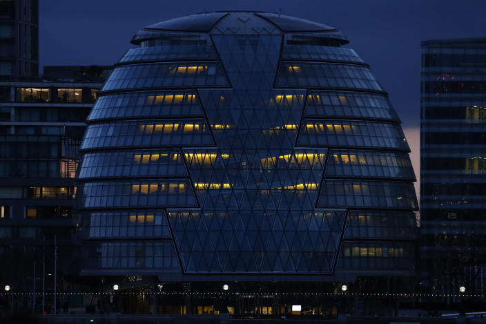City Hall on the south bank of the Thames in London is illuminated in the evening of Saturday, March 6, 2021. (AP Photo/Alastair Grant)
