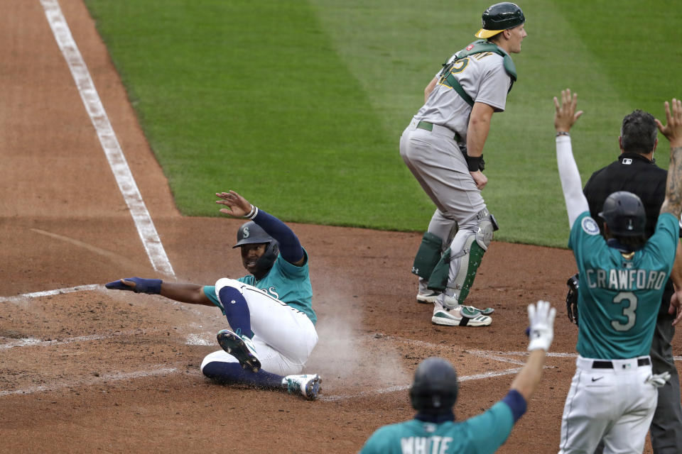 Seattle Mariners' Kyle Lewis slides safely home to score as Oakland Athletics catcher Sean Murphy waits for the ball in the fourth inning of a baseball game during the Mariners home opener Friday, July 31, 2020, in Seattle. (AP Photo/Elaine Thompson)