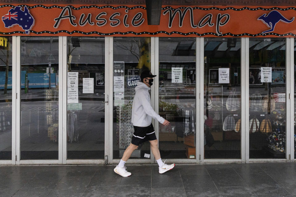 A man walks past a shop closed down store selling Australian paraphernalia items aimed at International tourists during lockdown in Melbourne, Australia, Wednesday, Aug. 5, 2020. Victoria state, Australia's coronavirus hot spot, announced on Monday that businesses will be closed and scaled down in a bid to curb the spread of the virus. (AP Photo/Asanka Brendon Ratnayake)