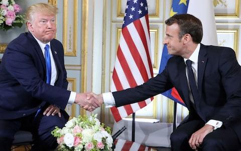 US President Donald Trump (L) and French President Emmanuel Macron shake hands during a meeting at the Prefecture of Caen, Normandy - Credit:  Ludovic MARIN / POOL / AFP