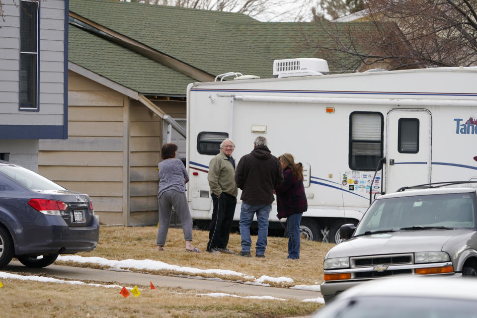 Neighbors gather on the lawn next to the home of Kirby Klements after a piece of debris crushed the man's pickup truck parked next to his home in Broomfield, Colo., as a passenger plane shed parts while making an emergency landing at nearby Denver International Airport Saturday, Feb. 20, 2021. (AP Photo/David Zalubowski)