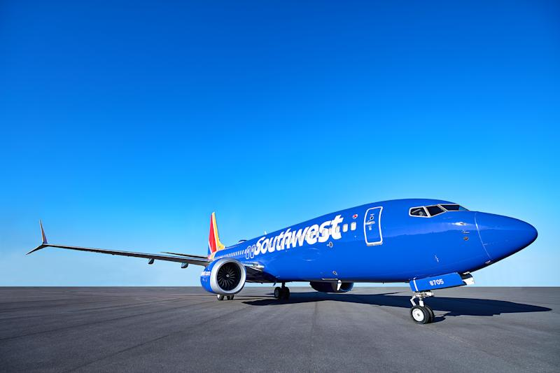 A blue Southwest Airlines 737 MAX 8 on a tarmac under blue skies.