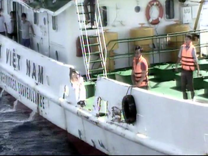 In this video image released by Vietnam Coast Guard, Vietnamese surveillance ship crew members stand near the side of the ship, allegedly damaged after being rammed by a Chinese ship, in the South China Sea, off Vietnam's coast, Wednesday, May 7, 2014. Chinese ships have been ramming into and firing water cannons at Vietnamese vessels trying to stop Beijing from putting an oil rig in the South China Sea, according to officials and video footage Wednesday, in a dangerous escalation of tensions over waters considered a global flashpoint. (AP Photo/Vietnam Coast Guard)