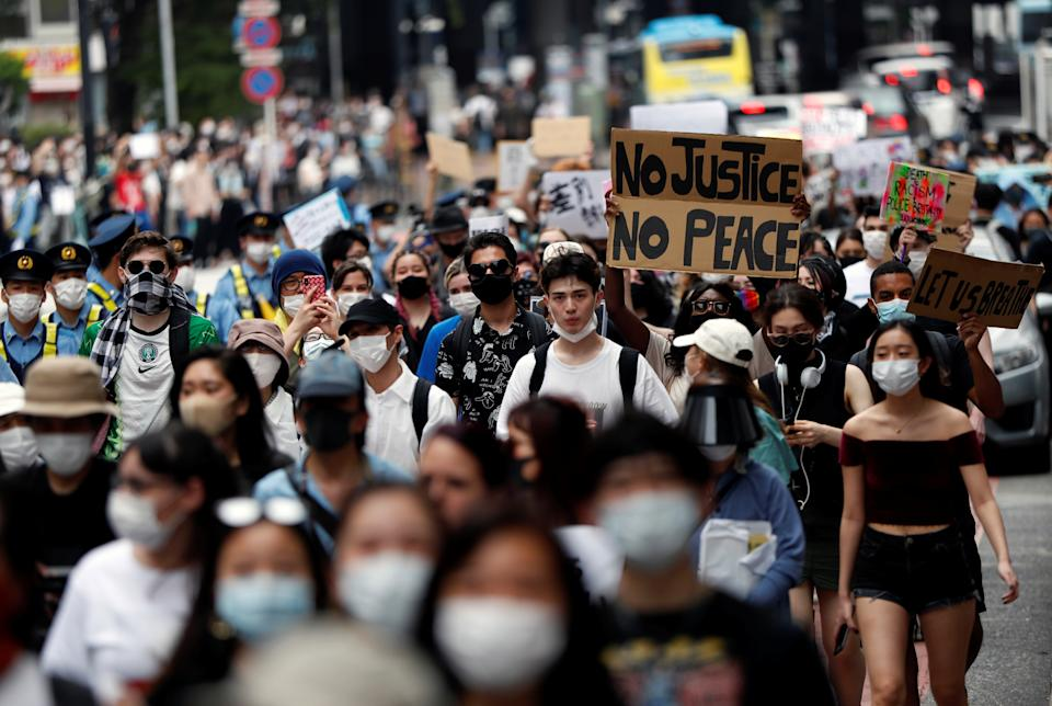 People wearing masks hold placards during a protest march over the alleged police abuse of a Turkish man, in echoes of a Black Lives Matter protest, following the death of George Floyd who died in police custody in Minneapolis, in Tokyo, Japan June 6, 2020.   REUTERS/Issei Kato